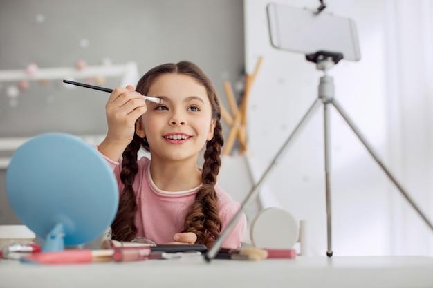 Menina bonita agindo como uma maquiadora na frente da câmera