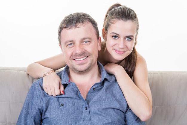 Menina bonita agradável adolescente sentado no sofá com o pai