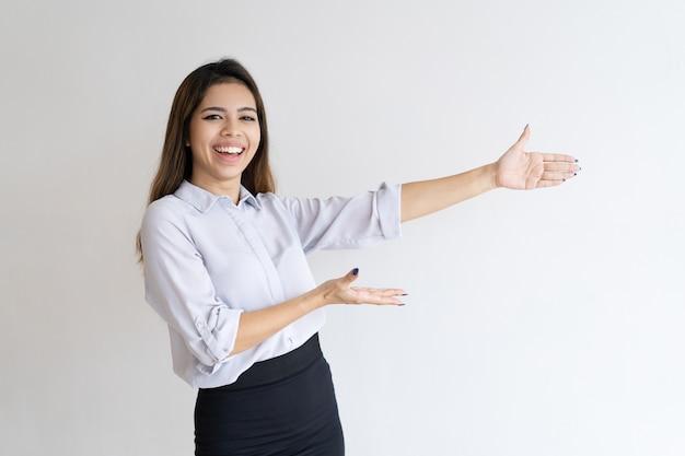 Menina bonita alegre apresentando novo produto