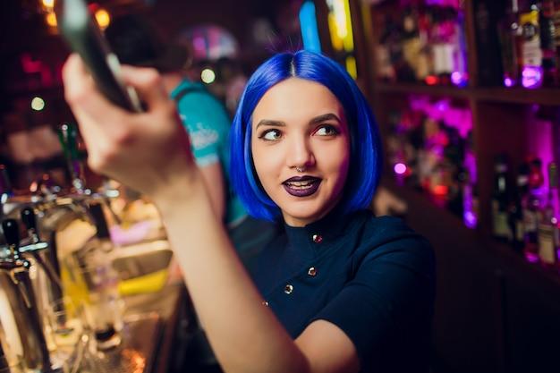Menina bonita alegre barman morena de camisa branca e gravata preta, servindo bebida de álcool no bar da boate, segurando a garrafa na mão, derramando bebida no copo