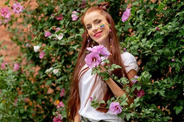 Menina bonita alegre com arco-íris lgbt no rosto, posando em flores desabrochando