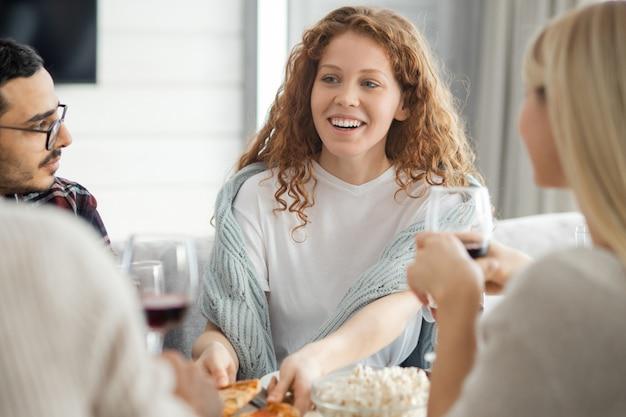 Menina bonita alegre com cabelo encaracolado pegando uma fatia de pizza enquanto compartilha novidades com amigos em uma reunião em casa