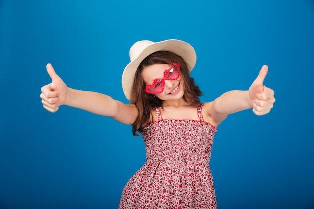 Menina bonita alegre com chapéu e óculos de sol em forma de coração mostrando os polegares para cima sobre um fundo azul
