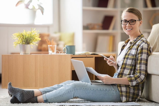 Menina bonita alegre de óculos sentada no tapete e olhando enquanto analisa suas finanças usando um aplicativo móvel e laptop