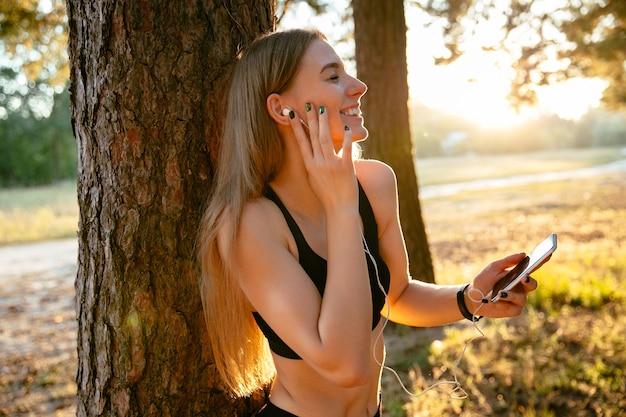 Menina bonita alegre no sportswear, desfrutando de ouvir música no telemóvel