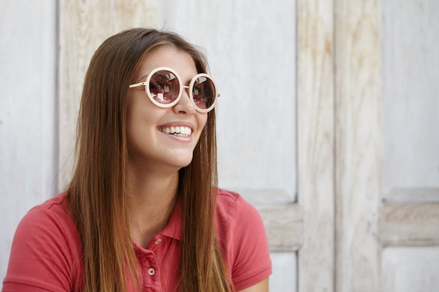 Menina bonita alegre usando óculos escuros redondos elegantes e sorrindo feliz enquanto se diverte dentro de casa