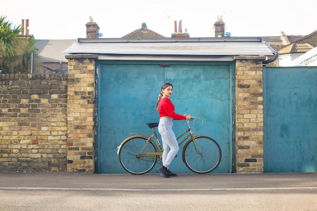 Menina bonita andando, carregando uma bicicleta