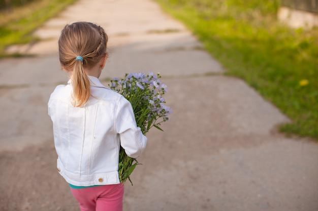 Menina bonita andando com um buquê de flores