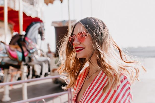Menina bonita andando em um parque de diversões. modelo feminino sorridente em óculos de sol cor de rosa da moda tem um bom dia no verão.