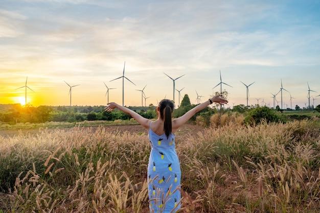 Menina bonita ande no prado e sorriu no fundo crepuscular é uma turbina eólica.