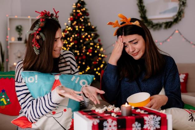 Menina bonita ansiosa com bandana de rena olha para pipoca caída sentada na poltrona com um amigo na época do natal em casa