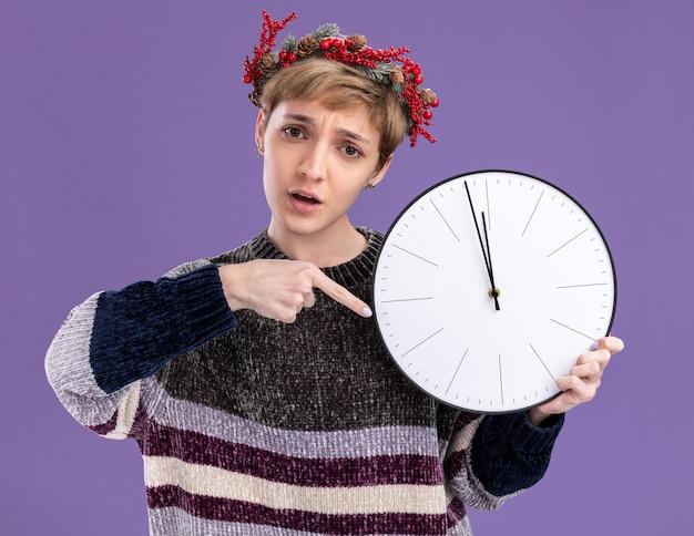 Menina bonita ansiosa com coroa de flores na cabeça de natal, segurando e apontando para o relógio, olhando para a câmera isolada no fundo roxo