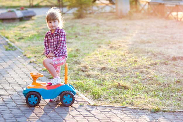 Menina bonita ao ar livre com um carro de brinquedo em um dia ensolarado