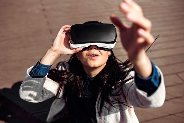 Menina bonita ao ar livre desfrutando de óculos de realidade virtual
