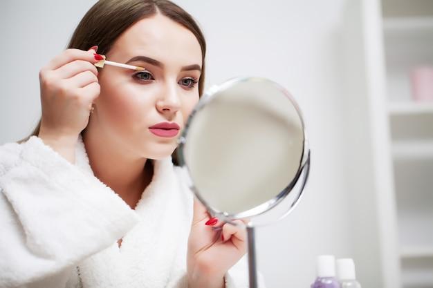 Menina bonita aplica maquiagem no rosto no banheiro do hotel