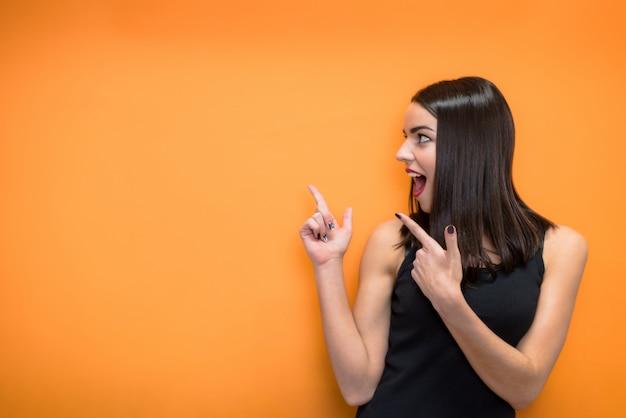 Menina bonita, apontando com os dedos em uma parede laranja com copyspace