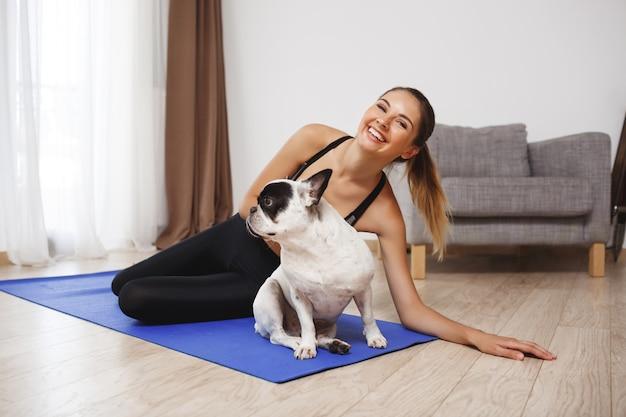 Menina bonita aptidão sentada no chão com cachorro
