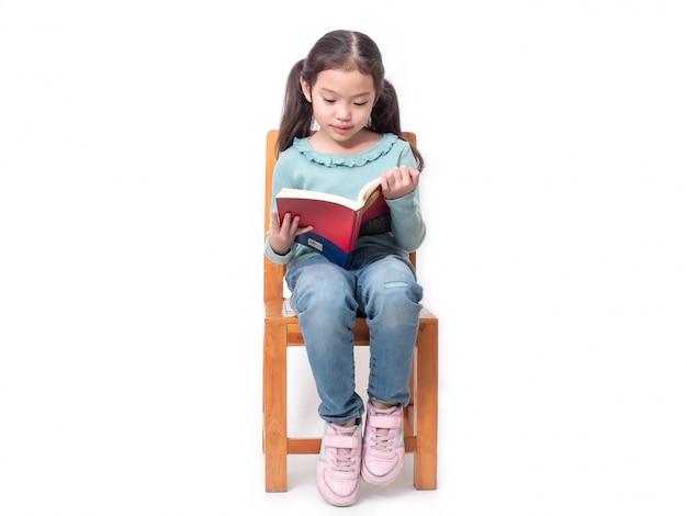 Menina bonita asiática 6 anos de idade, sentado na cadeira de madeira e lendo o livro.