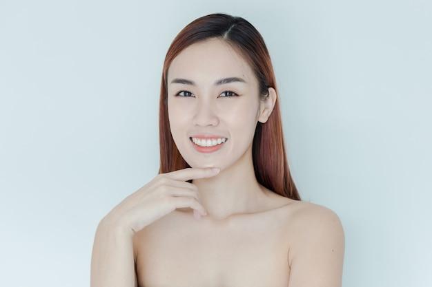 Menina bonita asiática com grandes olhos e sobrancelhas escuras, com ombros nus, mulher bonita olhando para a câmera e sorrindo