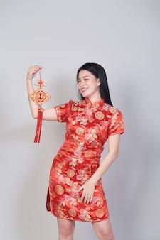 Menina bonita asiática com vestido tradicional chinês cheongsam ou qipao segurando foguete. conceito de ano novo chinês, modelo feminino isolado no fundo cinza do estúdio