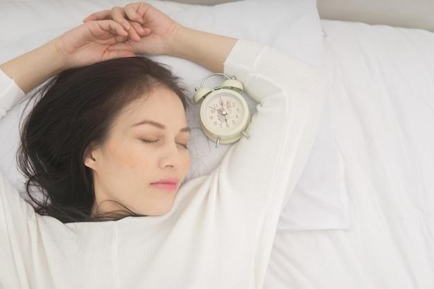 Menina bonita asiática dorme no quarto, deitada na cama