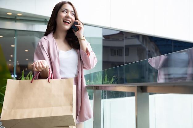Menina bonita asiática falando ao telefone com o amigo e segurando a sacola de compras