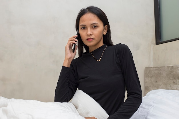 Menina bonita asiática infeliz se sentindo triste usando o smartphone na cama