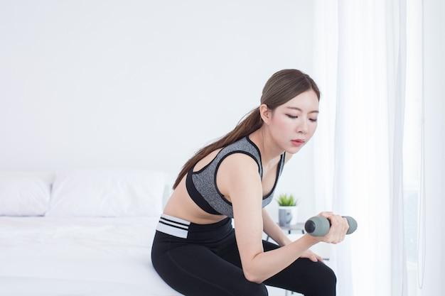 Menina bonita asiática jovem fitness levantando halteres no quarto