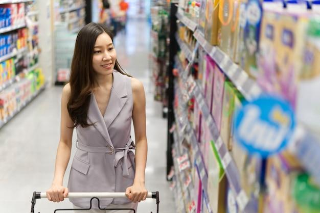 Menina bonita asiática nova que empurra o carrinho de compras que anda no supermercado.