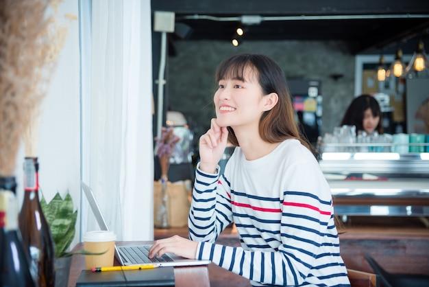 Menina bonita asiática nova que sorri ao trabalhar com o laptop na cafetaria