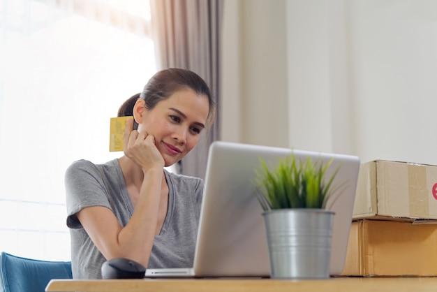 Menina bonita asiática que compra em linha do web site usando o cartão de crédito para o pagamento.
