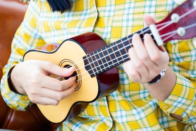Menina bonita asiática tocando ukulele de madeira na sala de estar.