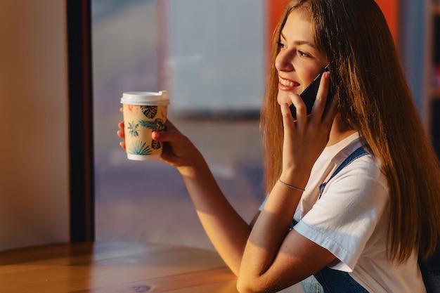 Menina bonita atraente jovem no café com café e telefone na manhã vigas