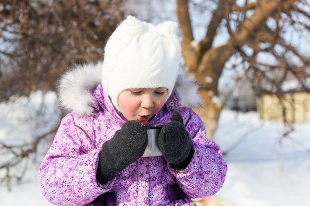 Menina bonita bebe chá na rua no inverno.