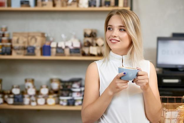 Menina bonita, bebendo café na loja, olhando para o lado.