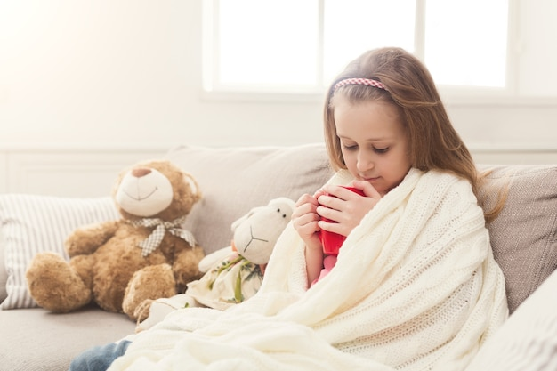 Menina bonita bebendo chá, sentado no sofá embrulhado em um cobertor de malha branca. linda criança pensativa, tendo o passatempo em casa no sofá com seus brinquedos, copie o espaço