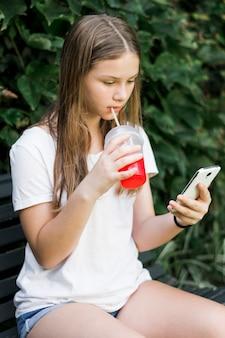 Menina bonita bebendo suco enquanto estiver usando smartphone no parque