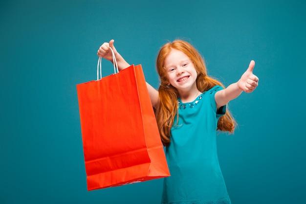 Menina bonita, bonita em roupas azuis com longos cabelos vermelhos cuida pacote