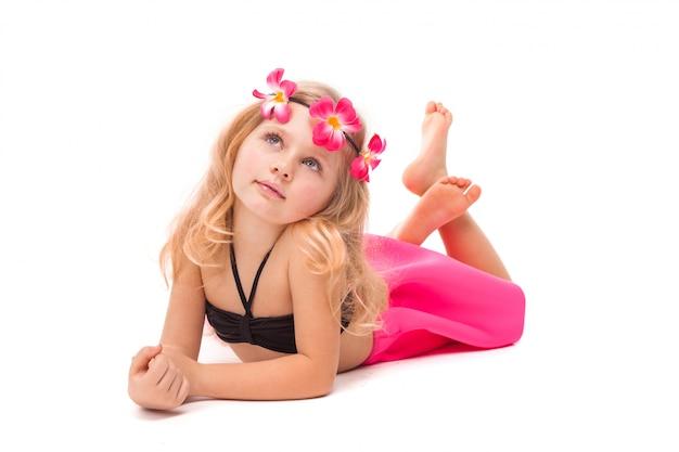 Menina bonita bonitinha em biquíni preto, saia rosa e grinalda rosa, mentiras