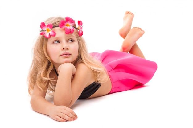 Menina bonita bonitinha em biquíni preto, saia rosa e grinalda rosa