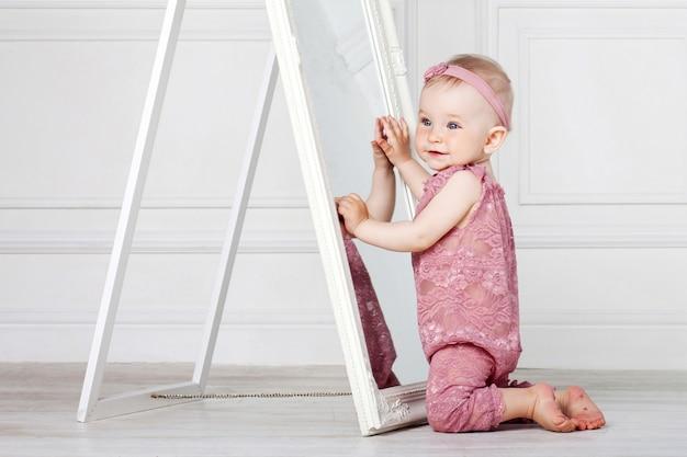 Menina bonita brinca com um espelho grande