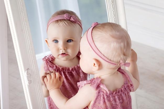 Menina bonita brinca com um grande espelho. retrato da menina com reflexo no espelho