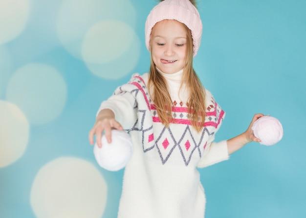 Menina bonita brincando com bolas de neve