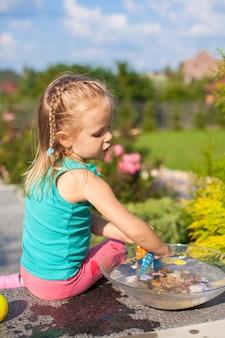 Menina bonita brincando com brinquedos no quintal