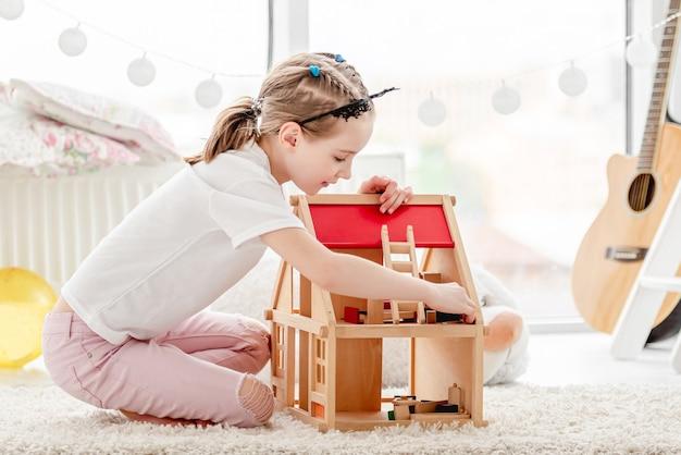 Menina bonita brincando com casa de bonecas de madeira no quarto das crianças