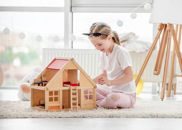Menina bonita brincando com casa de bonecas