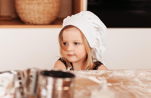 Menina bonita brincando com farinha na cozinha com um avental branco e chapéu de chef