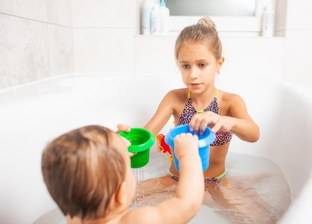 Menina bonita brincando com seu irmão mais novo no banheiro com água e brinquedos diferentes