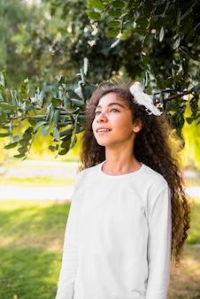 Menina bonita brincando com seus cabelos encaracolados em pé na frente da árvore