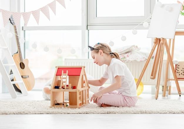 Menina bonita brincando com uma casa de bonecas